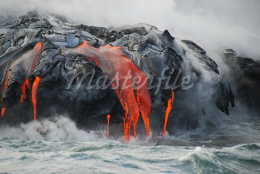 Red hot lava from Kilauea Volcano on the Big Island of Hawaii flows through lava tubes and pours like rivers into the ocean, bringing up clouds of steam and toxic gas, creating acres of lava rock and adding new land to the island. Stock Photo - Royalty-Free, Artist: claudio                       , Code: 400-05732741