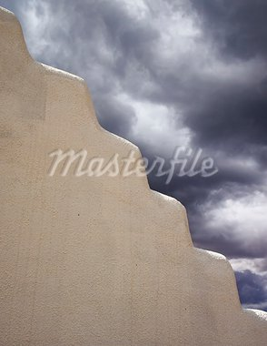 Contrast between a white adobe wall and dark storm clouds in the background. Can be used as a symbol of calm and turmoil. Stock Photo - Royalty-Free, Artist: searagen                      , Code: 400-05732912