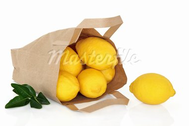 Lemon fruit in a brown paper recycled paper bag with leaf sprig isolated over white background. Stock Photo - Royalty-Free, Artist: marilyna                      , Code: 400-05734330