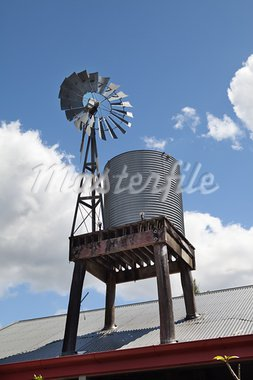 windmill pomping water towards tank on a tin roof with blue sky and clouds in rural dry Australia Stock Photo - Royalty-Free, Artist: kikkerdirk                    , Code: 400-05735758