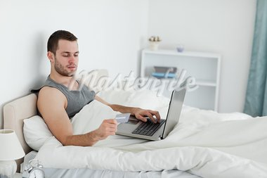 Young man purchasing online in his bedroom Stock Photo - Royalty-Free, Artist: 4774344sean                   , Code: 400-05737461