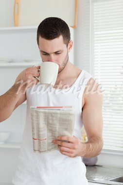 Portrait of a man drinking tea while reading the news in his kitchen Stock Photo - Royalty-Free, Artist: 4774344sean                   , Code: 400-05737571