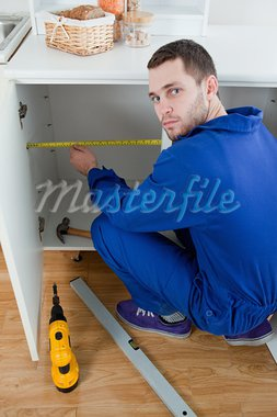 Portrait of a young repair man measuring something in a kitchen Stock Photo - Royalty-Free, Artist: 4774344sean                   , Code: 400-05737662