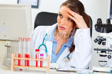 Concentrated doctor woman sitting in office and working on computer   Stock Photo - Royalty-Free, Artist: citalliance                   , Code: 400-05739349