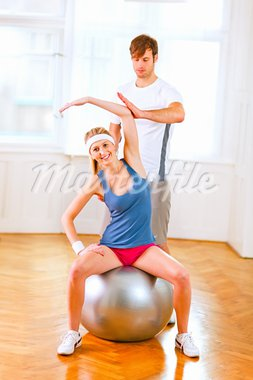 Smiling girl making exercises on fitness ball assisted by her personal trainer    Stock Photo - Royalty-Free, Artist: citalliance                   , Code: 400-05740612