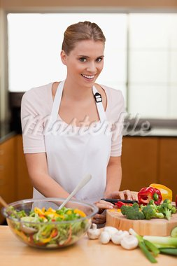 Portrait of a cute woman slicing vegetables in her kitchen Stock Photo - Royalty-Free, Artist: 4774344sean                   , Code: 400-05741817