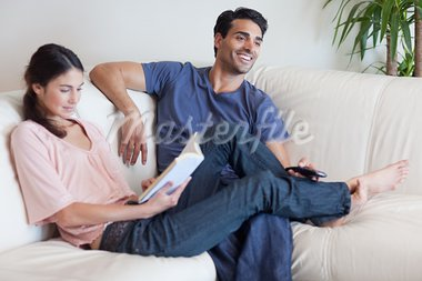 Woman reading a book while her husband is watching television in their living room Stock Photo - Royalty-Free, Artist: 4774344sean                   , Code: 400-05742037