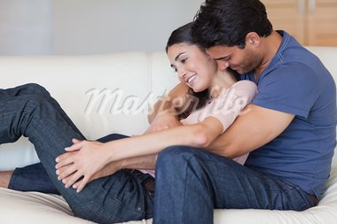 Man kissing his girlfriend in the neck in their living room Stock Photo - Royalty-Free, Artist: 4774344sean                   , Code: 400-05742615
