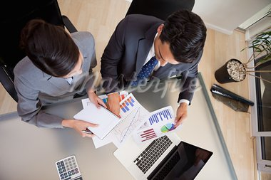 Focused sales persons studying statistics in an office Stock Photo - Royalty-Free, Artist: 4774344sean                   , Code: 400-05742764