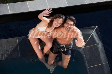 Above view of a smiling couple waving at the camera in a swimming pool Stock Photo - Royalty-Free, Artist: 4774344sean                   , Code: 400-05742810