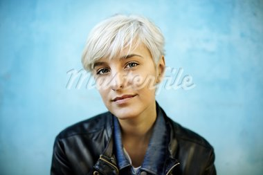 Young woman leaning on grungy blue wall. Selective focus Stock Photo - Royalty-Free, Artist: Kuzma                         , Code: 400-05743962