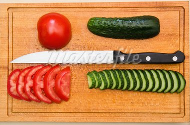 red tomato and green cucumbers slices with knife on board Stock Photo - Royalty-Free, Artist: mycola                        , Code: 400-05744318