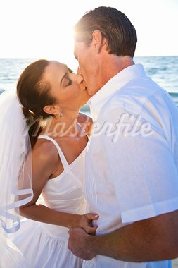 A married couple, bride and groom, kissing at sunset on a beautiful tropical beach Stock Photo - Royalty-Free, Artist: darrenbaker                   , Code: 400-05745198