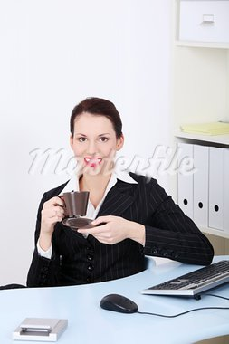 Front view portrait of a beautiful young smiling business woman sitting behind the desk during coffee break. Stock Photo - Royalty-Free, Artist: BDS                           , Code: 400-05745312