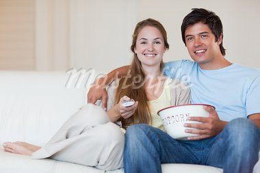 Young couple watching television while eating popcorn in their living room Stock Photo - Royalty-Free, Artist: 4774344sean                   , Code: 400-05746671