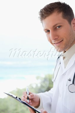 Side view of doctor with pen and clipboard Stock Photo - Royalty-Free, Artist: 4774344sean                   , Code: 400-05748246