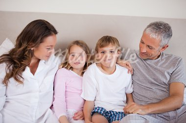 Smiling family lying on a bed in the morning Stock Photo - Royalty-Free, Artist: 4774344sean                   , Code: 400-05749413