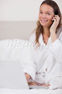 Portrait of a woman using a notebook while making a phone call in her bedroom Stock Photo - Royalty-Free, Artist: 4774344sean                   , Code: 400-05749465