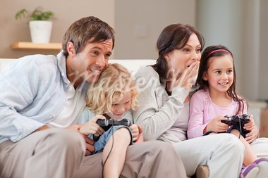 Competitive family playing video games in a living room Stock Photo - Royalty-Free, Artist: 4774344sean                   , Code: 400-05749667