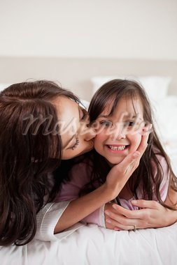 Portrait of a mother kissing her daughter in a bedroom Stock Photo - Royalty-Free, Artist: 4774344sean                   , Code: 400-05749805