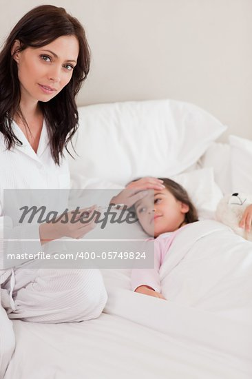 Portrait of a concerned mother checking on her daughter's temperature in a bedroom Stock Photo - Royalty-Free, Artist: 4774344sean                   , Code: 400-05749824