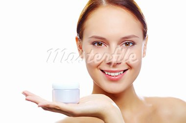 Fresh woman holding container with facial cream and looking at camera Stock Photo - Royalty-Free, Artist: pressmaster                   , Code: 400-05750023
