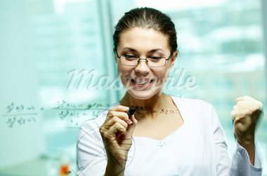 Happy young woman looking at board while writing on it Stock Photo - Royalty-Free, Artist: pressmaster                   , Code: 400-05750063