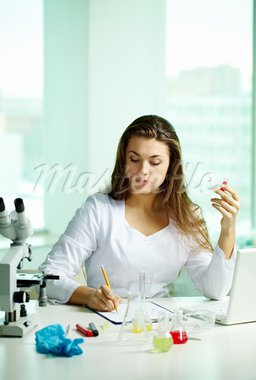 Serious chemist making notes while describing substances Stock Photo - Royalty-Free, Artist: pressmaster                   , Code: 400-05750065
