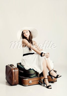 Fashion woman sitting over her luggage and waiting, isolated on a grey background Stock Photo - Royalty-Free, Artist: iko                           , Code: 400-05750463