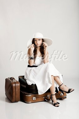 Fashion woman sitting over her luggage and waiting, isolated on a grey background Stock Photo - Royalty-Free, Artist: iko                           , Code: 400-05750465