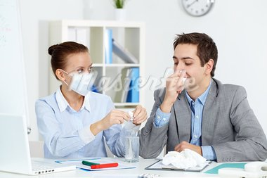 Image of sick businessman with tissue looking at his colleague in mask dissolving solution for him in office Stock Photo - Royalty-Free, Artist: pressmaster                   , Code: 400-05750921