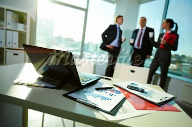 Image of business documents on workplace with three partners interacting on background Stock Photo - Royalty-Free, Artist: pressmaster                   , Code: 400-05751019