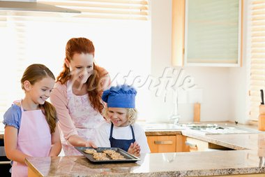 Smiling mother presenting finished cookies to her children Stock Photo - Royalty-Free, Artist: 4774344sean                   , Code: 400-05751232