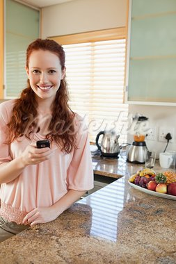 Smiling woman in the kitchen with her cellphone Stock Photo - Royalty-Free, Artist: 4774344sean                   , Code: 400-05751463