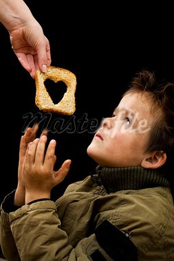 Feeding the poor concept with dirty kid receiving slice of bread - on black Stock Photo - Royalty-Free, Artist: lightkeeper                   , Code: 400-05752349