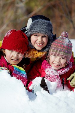 Happy friends in winterwear playing in snowdrift outside Stock Photo - Royalty-Free, Artist: pressmaster                   , Code: 400-05753654