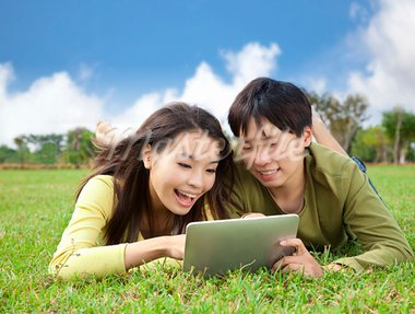 young asian student using tablet computer while lying in the park Stock Photo - Royalty-Free, Artist: tomwang                       , Code: 400-05754466