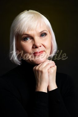 Portrait of mature blond female looking at camera on black background Stock Photo - Royalty-Free, Artist: pressmaster                   , Code: 400-05754982