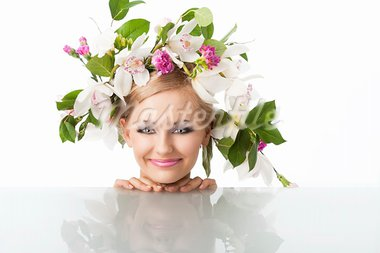 young sexy beautiful woman with naked shoulder and wearing a big crown of flower and leaves as spring queen, she is behind the table, her face is resting on the table and she smiles and looks in to the lens Stock Photo - Royalty-Free, Artist: carlodapino                   , Code: 400-05755509