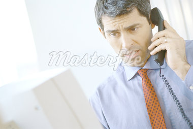 Businessman using phone, frowning and looking at computer Stock Photo - Premium Royalty-Freenull, Code: 695-05764485