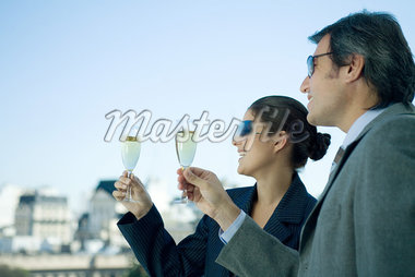 Business partners holding up glasses of champagne, skyline in background Stock Photo - Premium Royalty-Freenull, Code: 695-05765193