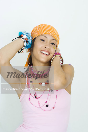 Teen girl wearing lots of accessories, hands behind head, smiling at camera, ...