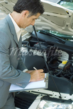 Mature man in suit inspecting car Stock Photo - Premium Royalty-Freenull, Code: 695-05766453