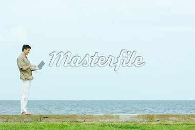 Man standing on low wall using laptop, body of water in background, full length Stock Photo - Premium Royalty-Freenull, Code: 695-05767499
