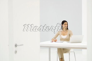 Female office worker sitting at desk, using laptop computer Stock Photo - Premium Royalty-Freenull, Code: 695-05768201