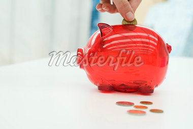 Person putting change in piggy bank, cropped Stock Photo - Premium Royalty-Freenull, Code: 695-05770541