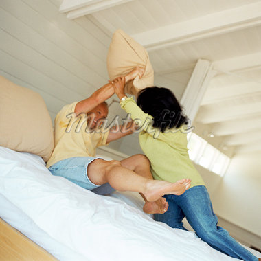 Couple having pillow fight on bed Stock Photo - Premium Royalty-Freenull, Code: 695-05774243