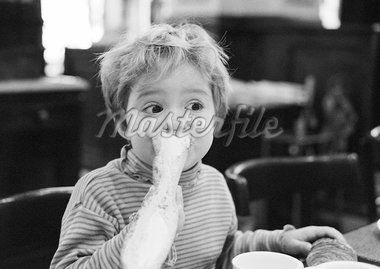 Young child eating bread, portrait, b&w. Stock Photo - Premium Royalty-Freenull, Code: 695-05774760