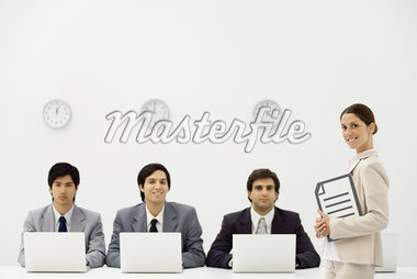 Professional men sitting with laptop computers beneath wall clocks, female supervisor smiling at camera Stock Photo - Premium Royalty-Freenull, Code: 695-05779410