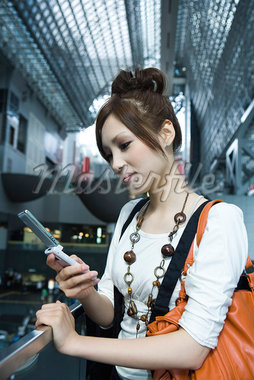 Young female text messaging on cell phone in shopping mall Stock Photo - Premium Royalty-Freenull, Code: 695-05779617